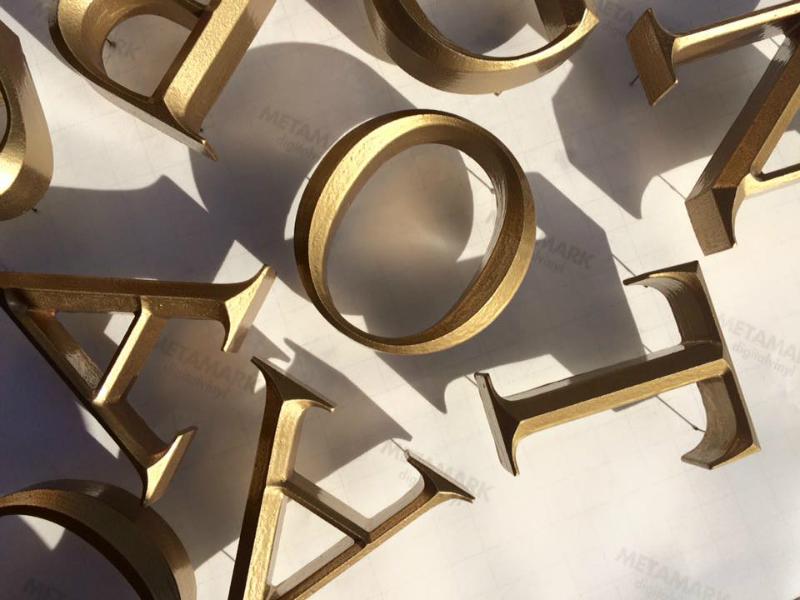 Prismatische bronzen doos letters
