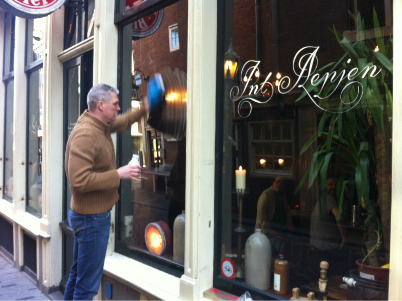Handpainting the window of Cafe in 't Aepjen in Amsterdam by hand